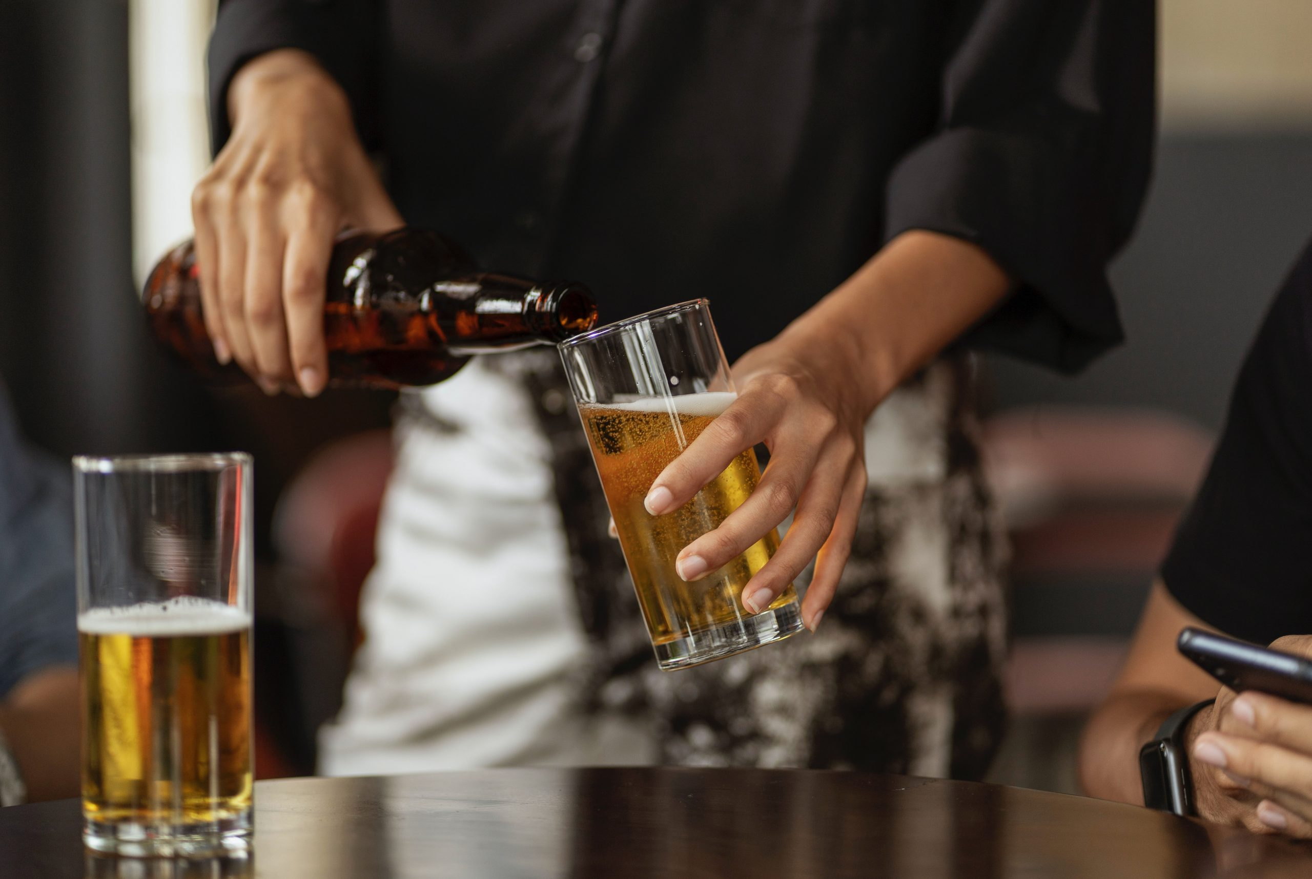 a man pouring light beer in a glass