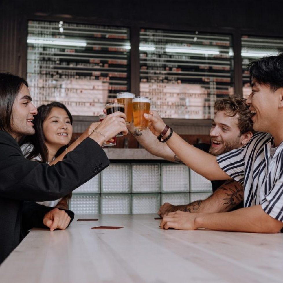 two girls and two guys drinking beer in pub